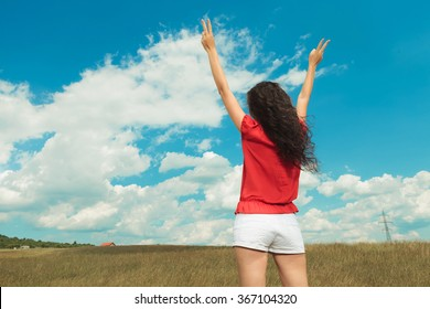back view of a woman dressed in white shorts with red blouse showing victory sign with both hands while standing in the fields