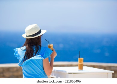 Back view of woman drinking cold coffee enjoying sea view. Beautiful woman relax during european sea vacation on the beach enjoying frappe