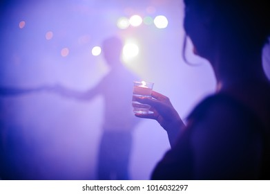 Back view of a woman drinking shot in a nightclub on the dance floor at the party