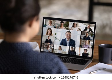 Back view of woman employee talk speak on video call with diverse multiracial colleague coworkers on computer. Female worker have webcam digital conference with team, engaged in group online meeting. - Shutterstock ID 1840196746