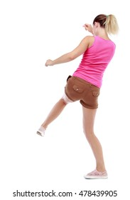 back view of woman funny fights waving his arms and legs. Isolated over white background. Sport blond in brown shorts hit his foot.