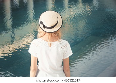 Back view of woman with hat looking at the water - summer vacation concept