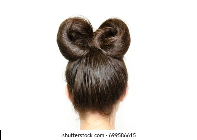 Back view of woman head with beautiful hairstyle. Bow or tie making from hair. Elegance and trendy haircut. Love and like Minnie Mouse.