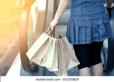 Back view of woman holding shopping bags on escalator in the shopping mall in vintage color tone