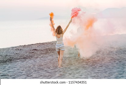 Back view of woman holding smoke bombs and dancing on beach party.