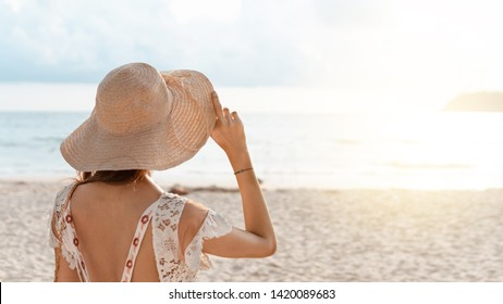 Back view of a woman is holding straw hat and wearing dress, relaxing on the beach in summer vacation. sunflare light.