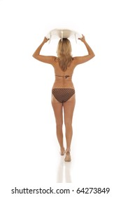 Back view of woman holding surfboard on head