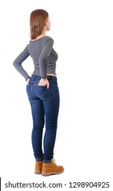 Back view of a woman in jeans.  girl  watching. Rear view people collection.  backside view of person. Isolated over white. Girl in a striped T-shirt stuck her hands in the back pockets of pants