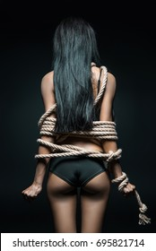back view of woman in lingerie bound with rope isolated on black