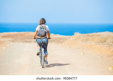 Back view of woman on bike outdoors smiling.