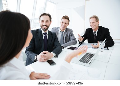 Back view of woman on conference with her colleagues in office