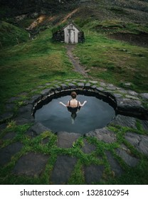 Back view of woman in outdoor bath near old ground house.