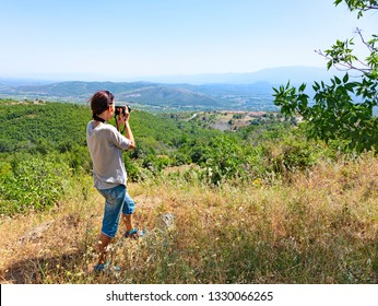 Back view of a woman photographer taking pictures of the valley with mountains. Europe. Greece.