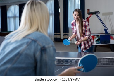 Back view of woman playing ping ping with cheerful girl standing at table.