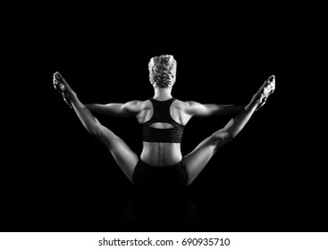 Back view of a woman practicing yoga in a black studio black and white picture