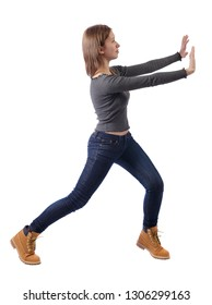 back view of woman pushes wall.  Isolated over white background. Rear view people collection. backside view of person. Girl in jeans and boots pushing the wall in front of her.