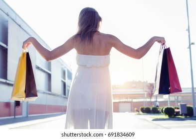 back view of woman raises the colorful shopping bags, payment and buy on sale or off discount, space for text