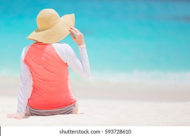 back view of woman in rashguard and sunhat enjoying picture perfect caribbean beach with turquoise water, vacation and sun protection concept, copyspace on the right