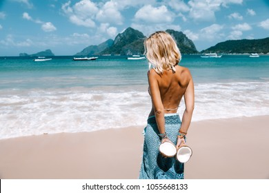 Back view of woman relaxing on the tropical beach, looking at sea landscape and eating coconut. Travelling tour in Asia: El Nido, Palawan, Philippines.