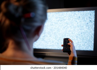 Back view of woman with remote control in front of TV set with noise on the screen