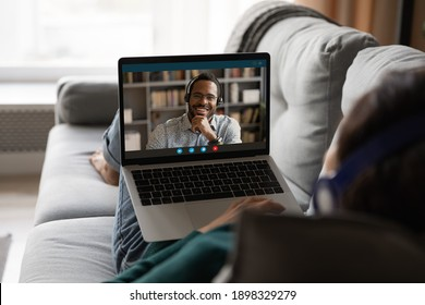 Back view of woman rest on sofa at home talk on video call using headphones. Female relax on couch have webcam digital virtual conference with male client or colleague on laptop.