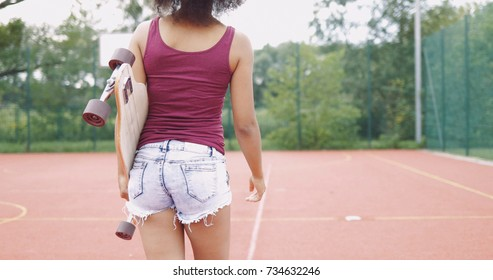 Back view of woman in shorts and tank top holding longboard and walking on background of sports ground in summertime.
