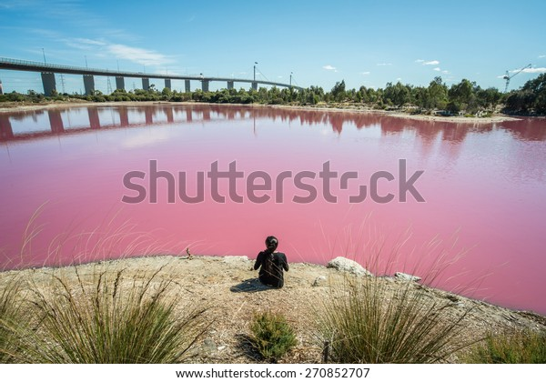 Back view of woman sitting at the edge of the salt pink lake at west gate park, Melbourne, Victoria state of Australia.