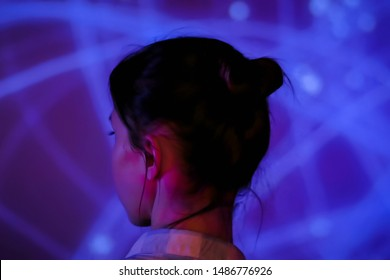 Back view - woman standing in front of interactive display and looking around at modern immersive exhibition with low light illumination. Education, digital art and entertainment concept