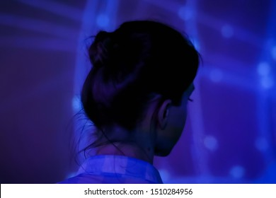 Back view - woman woman standing in front of interactive display and looking around at modern immersive exhibition with low light illumination. Education, technology, art and entertainment concept