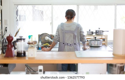 Back view of a woman standing in the kitchen