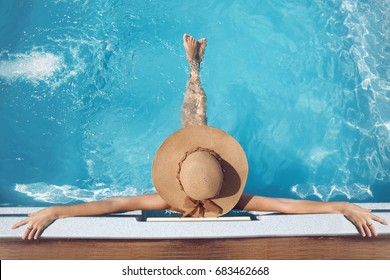 Back view of woman in straw hat relaxing in swimming pool on Tropical Resort. Exotic Paradise. Travel, Tourism and Vacations Concept.