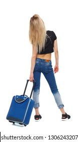 Back view of woman with suitcase. Standing young girl. Rear view people collection.  backside view of person. Isolated over white background. Blonde girl tourist looks up at the board of flights