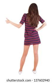 Back view of  woman thumbs up. Rear view people collection. backside view of person. Isolated over white background. slender brunette in a striped dress shows the symbol of success or hitchhiking