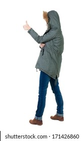 Back view of  woman thumbs up. Rear view people collection. backside view of person. Isolated over white background. slender brunette in a parka shows the symbol of success or hitchhiking