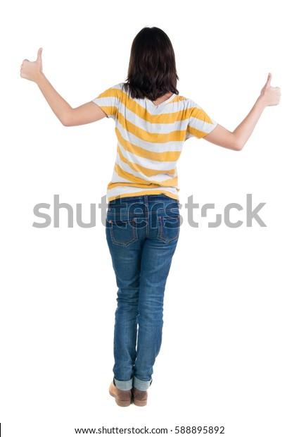 Back view of  woman thumbs up. Rear view people collection. backside view of person. Isolated over white background. slender brunette in a jeans shows the symbol of success or hitchhiking