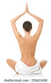 Back view of a woman in towel practising yoga.
