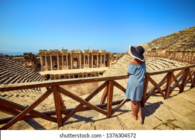 Back view of woman traveler in hat looking at amazing Amphitheater ruins in ancient Hierapolis, Pamukkale, Turkey. Grand panorama