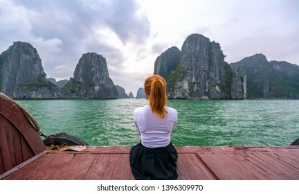 Back view woman traveler sitting on boat looking at Halong Bay in Vietnam among the islands.
