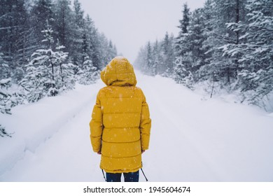 Back view of woman in trendy yellow coat spending time in wood with tall frozen trees during vacation trip, female walking on snowy road explore wanderlust location during holidays