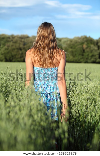 Back view of a woman walking across an oat meadow with the blue sky in the background