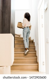 back view of woman walking upstairs while holding box
