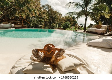 Back view woman wearing straw hat lie on sunbed  and enjoy sun tan near swimming pool with view on ocean and palm trees.  Relaxing summer day, Luxurious tropical vacation concept