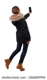 Back view woman in winter jacket who makes selfie with a smartphone. girl  watching.  Isolated over white background. The girl in the black jacket holds a smartphone and poses taking pictures.
