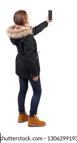 Back view woman in winter jacket who makes selfie with a smartphone. girl  watching. Rear view people collection.    Isolated over white background. Girl in warm park with fur takes a picture by phone