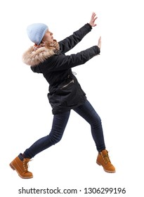 back view of woman in winter jacket pushes wall.  Isolated over white background. Rear view people collection.  A girl in a warm park with fur is protected by her hands from something above.