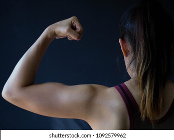 Back view Woman's arm showing muscle on dark background. Healthy concept. fitness.
