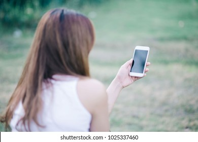 The back view of a woman's hand looking at the media on a smart phone. Play in the park.