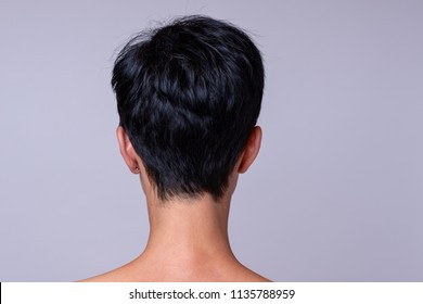 Back view of a womans head in short darker hair over neutral background