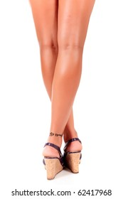 Back view of a woman's tanned legs with a tattoo, her ankles crossed while wearing high heels summer shoes. Studio shot. White background.