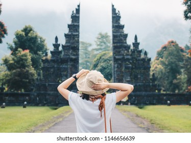 Back view of women enjoy her holiday in Bali with the view of traditional Hindu gate in Bali island, Indonesia.